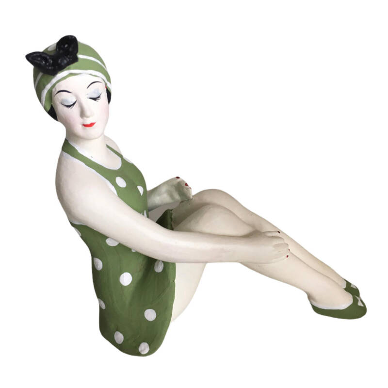 Badenixe klein, sitzend, in einem grün/weissen Badeanzug